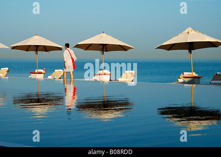 Tourist walking between deck chairs and shade umbrellas reflected in the Chedi Hotel swimming pool with a view over - Stock Photo