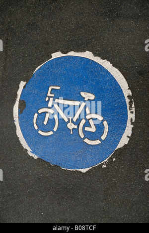 Worn-out, weathered symbol indicating a bike path, painted on pavement, asphalt - Stock Photo