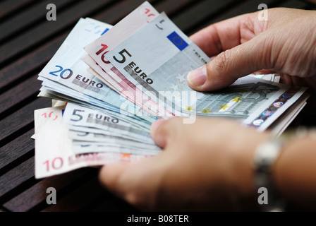 Woman counting money, Euro banknotes - Stock Photo