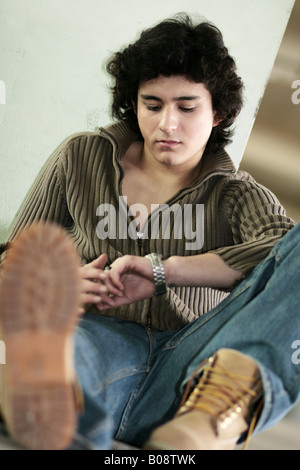 joung man, leaning on a wall looking for the time - Stock Photo