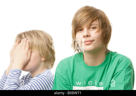 10 and 13-year-old boys, 10-year-old covering his face with his hands - Stock Photo