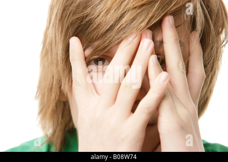 13-year-old boy covering his face with his hands - Stock Photo