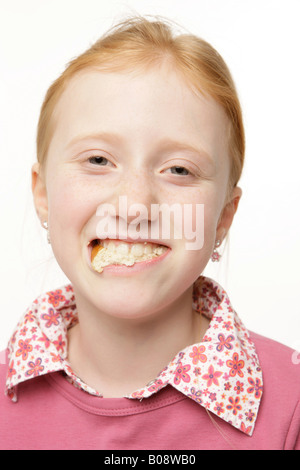 8-year-old red-haired girl with bread in her mouth - Stock Photo