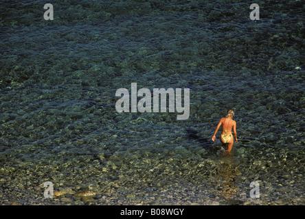 Young woman wearing a bikini wading through clear Mediterranean waters, Cyprus - Stock Photo