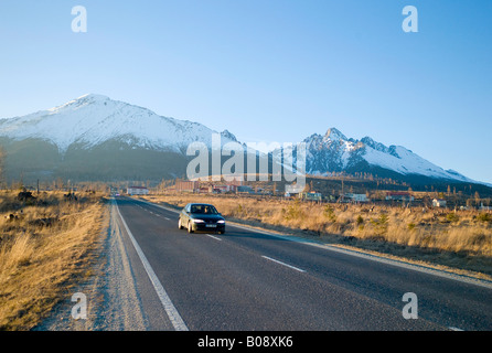 Car driving along a straight road leading to Tatranská Lomnica, with Carpathian Mountains, High Tatra peaks (back), - Stock Photo
