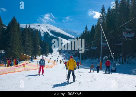 Skiers skiing down the Lukova ski run, Jasna Ski Resort, Lower Tatras, Slovakia - Stock Photo