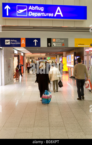 Passenger pulling her carry-on luggage to her departure gate, Frankfurt International Airport, Hesse, Germany - Stock Photo