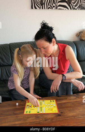 Mother with child, 10 years old, playing Ludo board game - Stock Photo