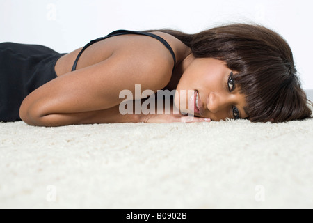 Young, dark-skinned woman wearing a black dress lying on a pale carpet - Stock Photo