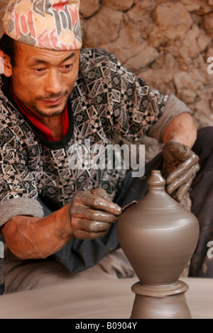Potter at work on an outdoor pottery square in Bhaktapur, Nepal - Stock Photo