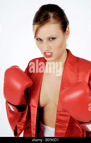Boxing, young woman dressed in a scant silk robe posing aggressively, bearing her teeth and clenching her gloved - Stock Photo