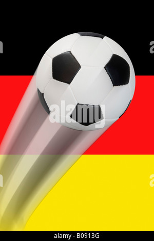 Football flying in front of a German flag - series - Stock Photo