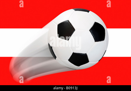 Football flying in front of an Austrian flag - series - Stock Photo