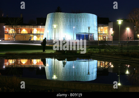 The new music school reflected on a pond's surface at night in Fellbach, Stuttgart, Baden-Wuerttemberg, Germany - Stock Photo