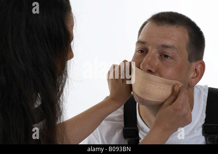 Woman sticking a big plaster, band-aid over a man's mouth - Stock Photo