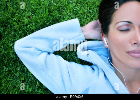 Woman lying on the grass and listening to music