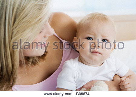 Young mother sitting with baby (6-12 months) in bedroom - Stock Photo