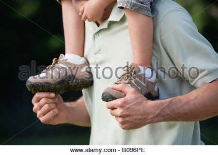 Father carrying son (4-7) on his shoulders, outdoors, close-up, detail - Stock Photo