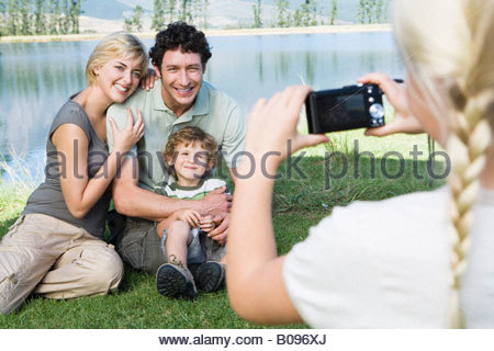 Girl photographing family outdoors, family posing for picture - Stock Photo