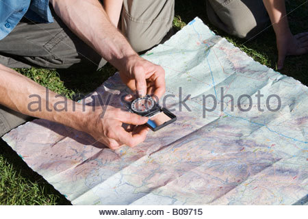 Man holding compass, looking at map, close-up from above - Stock Photo