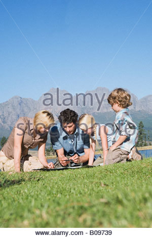 Young Family sitting on grass looking at map, outdoors - Stock Photo