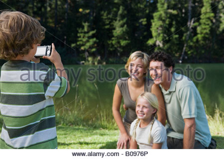 Boy photographing family outdoors, mother, father and sister posing for picture - Stock Photo