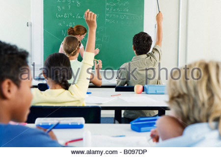 Group of school children (10-13) in classroom with hands raised - Stock Photo