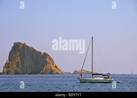 Sailing yacht navigating past an unusual island near Stromboli Island, Southern Italy - Stock Photo
