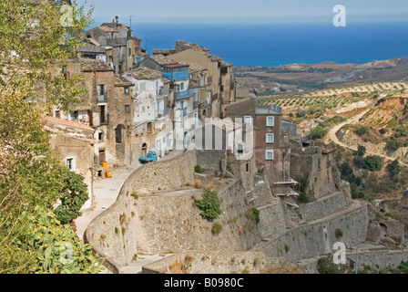 Mountain village built on very steep terraces, view of orchards and sea at back, Povalino, Calabria, Southern Italy - Stock Photo