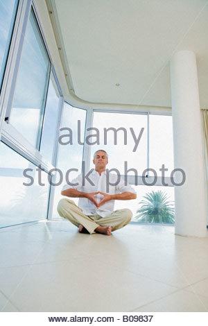 Senior man sitting, doing Yoga exercise, indoors - Stock Photo
