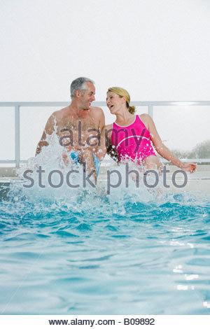 Senior couple sitting on edge of swimming pool laughing and splashing - Stock Photo