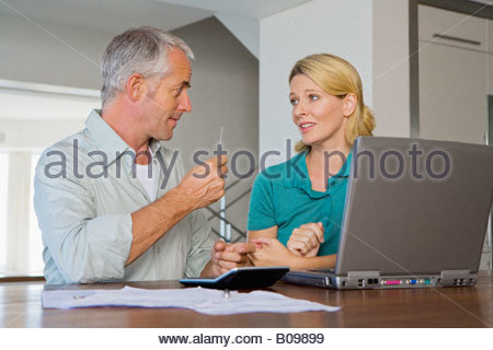 Mature couple arguing about financial situation, using calculator and Laptop - Stock Photo