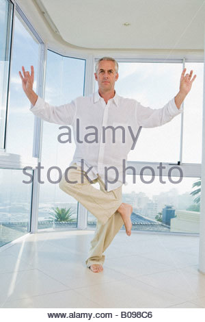 Senior man standing on one leg, doing Yoga exercise, indoors - Stock Photo