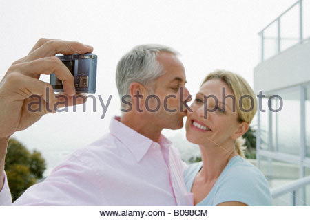 Mature couple on terrace smiling while taking self portrait with camera phone - Stock Photo