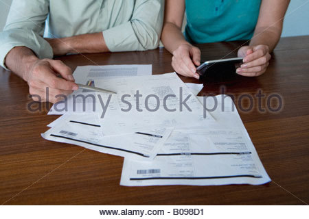 Mature couple looking at bills, using calculator, detail of hands - Stock Photo