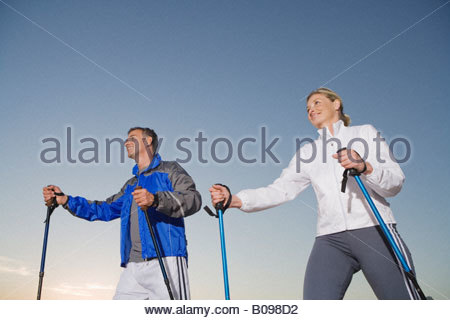 Senior couple wearing tracksuit doing Nordic Walking at sunset - Stock Photo