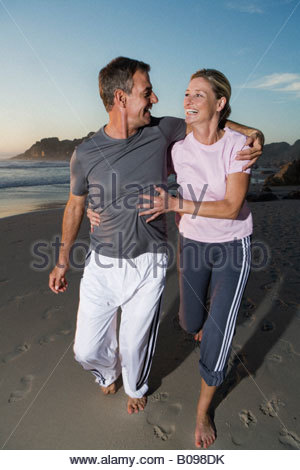 Senior couple laughing while jogging along beach at sunset - Stock Photo