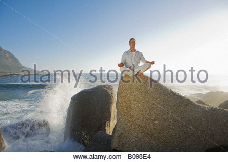 Mature man sitting doing yoga on top of rock outcrop  with waves in background - Stock Photo