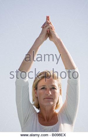Mature woman arms raised doing Yoga exercises portrait - Stock Photo