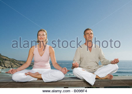 Mature couple sitting cross-legged on wooden bench outdoors doing yoga - Stock Photo