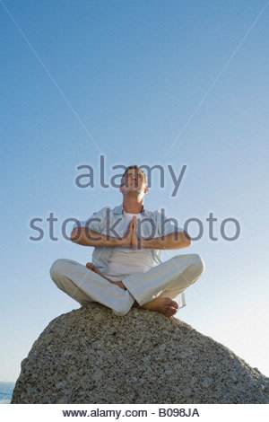 Mature man sitting on rock doing yoga exercise with blue sky in background - Stock Photo
