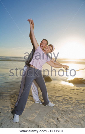 Senior couple laughing and having fun on beach at sunset - Stock Photo