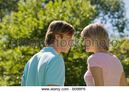 Young couple facing each other, smilling with tree in background - Stock Photo