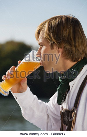 Young man in traditional Bavarian outfit, drinking wheat beer, side profile - Stock Photo