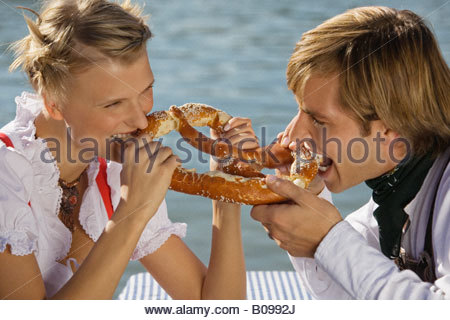 Young couple in traditional Bavarian outfit, eating Prezel, Munich - Stock Photo