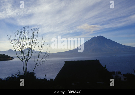 View across lake from shore to shore Volcanic silhouettes against sky LAKE ATITLAN GUATEMALA - Stock Photo