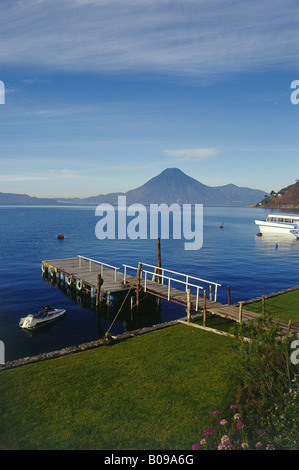 View across lake from shore to shore Volcanic silhouettes against sky Passenger boat Calm water LAKE ATITLAN GUATEMALA - Stock Photo