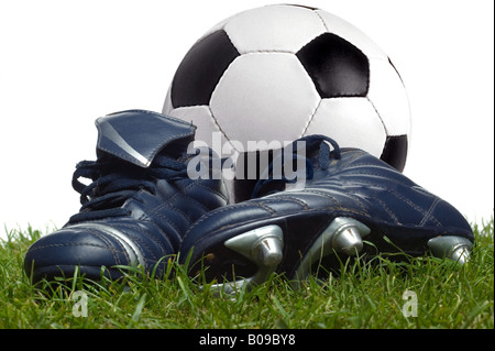 A pair of boots and a football on the grass studio shot - Stock Photo
