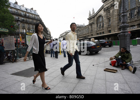 A beggar on the sidewalk and people walking by, Paris, France - Stock Photo