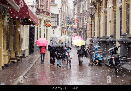 Amsterdam, Gravenstraat street in falling snow, pedestrians umbrellas, bicycles - Stock Photo